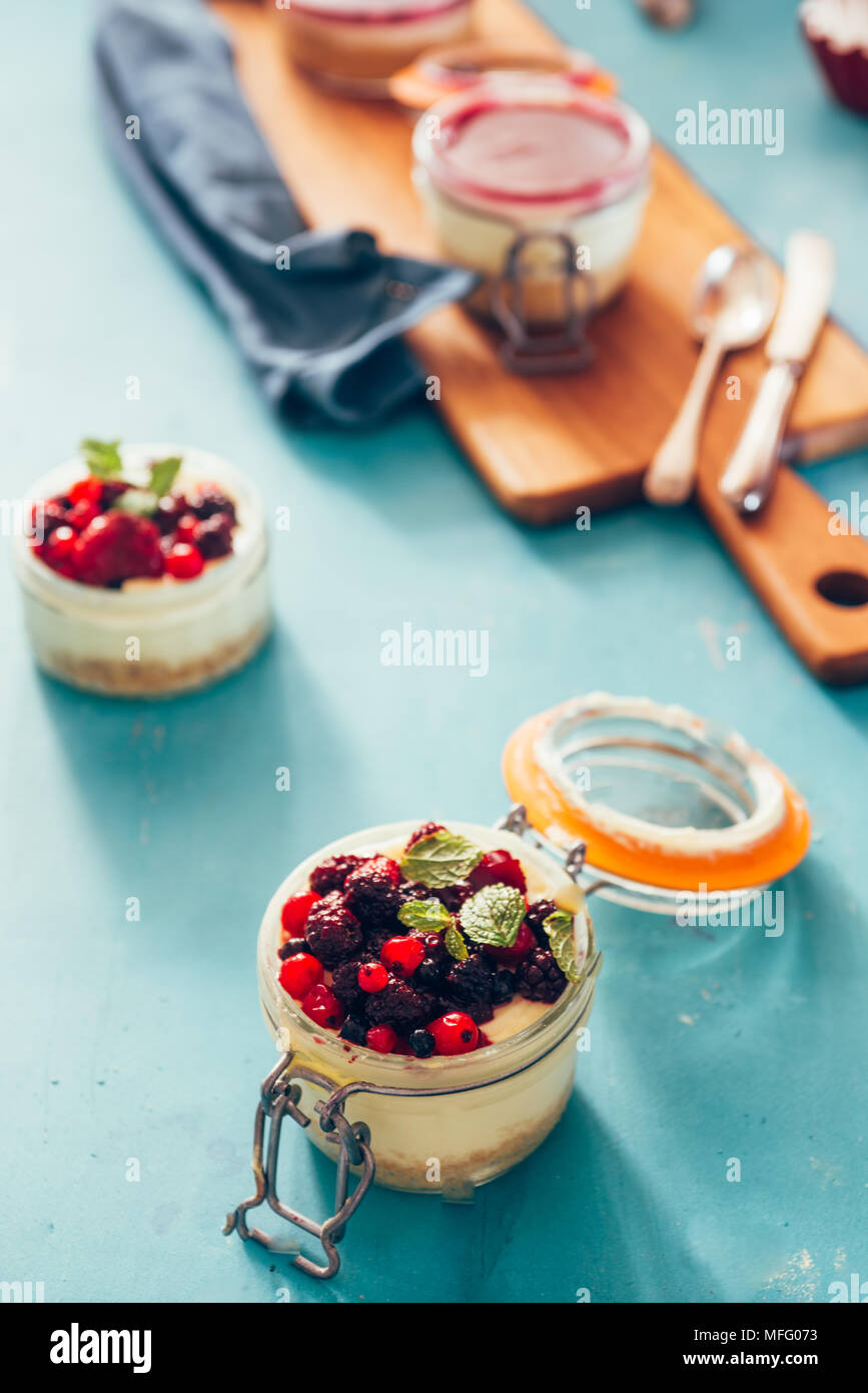 Cheesecake with a top made of berries gelatin on a jar over an aqua rusty background, natural light only. - Stock Image