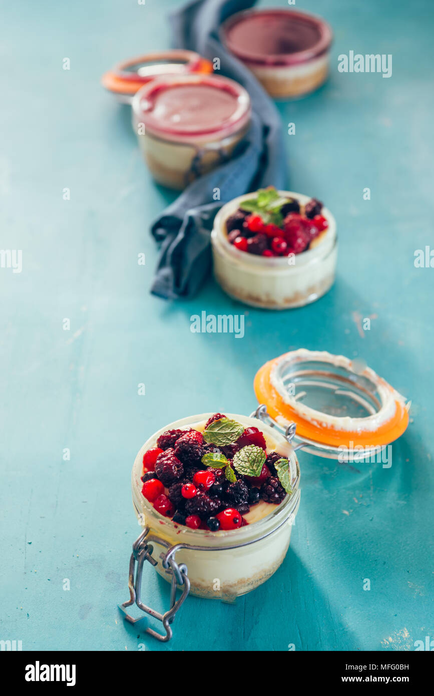 Cheesecake with a top filled  of berries  on a jar over an aqua rusty background, natural light only. - Stock Image