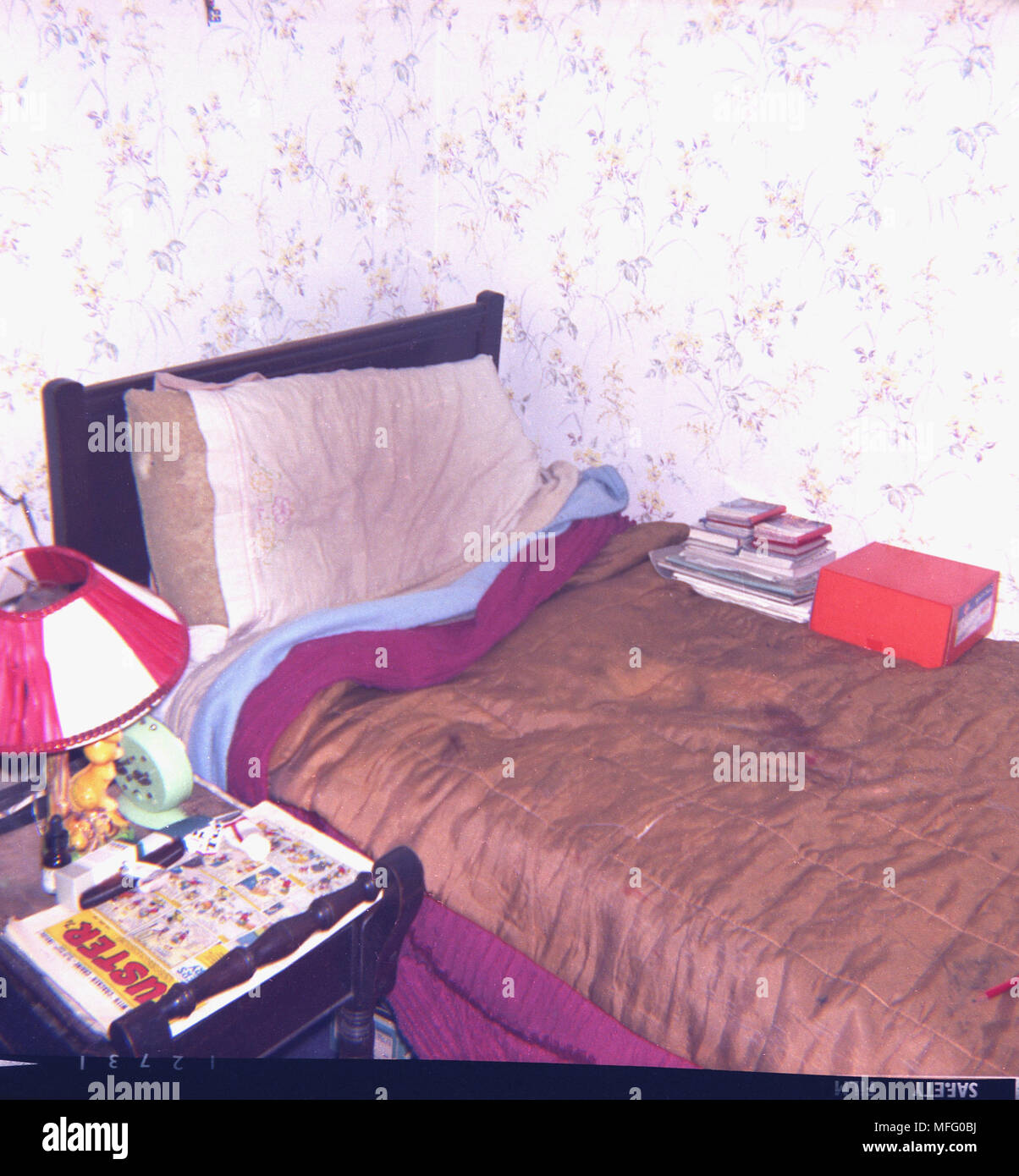 1970s, picture shows a scruffy, untidy single bed in a corner of a room, with a shiny brown blanket cover over it, ansd with a Buster comic on the bedside table, England, UK. - Stock Image