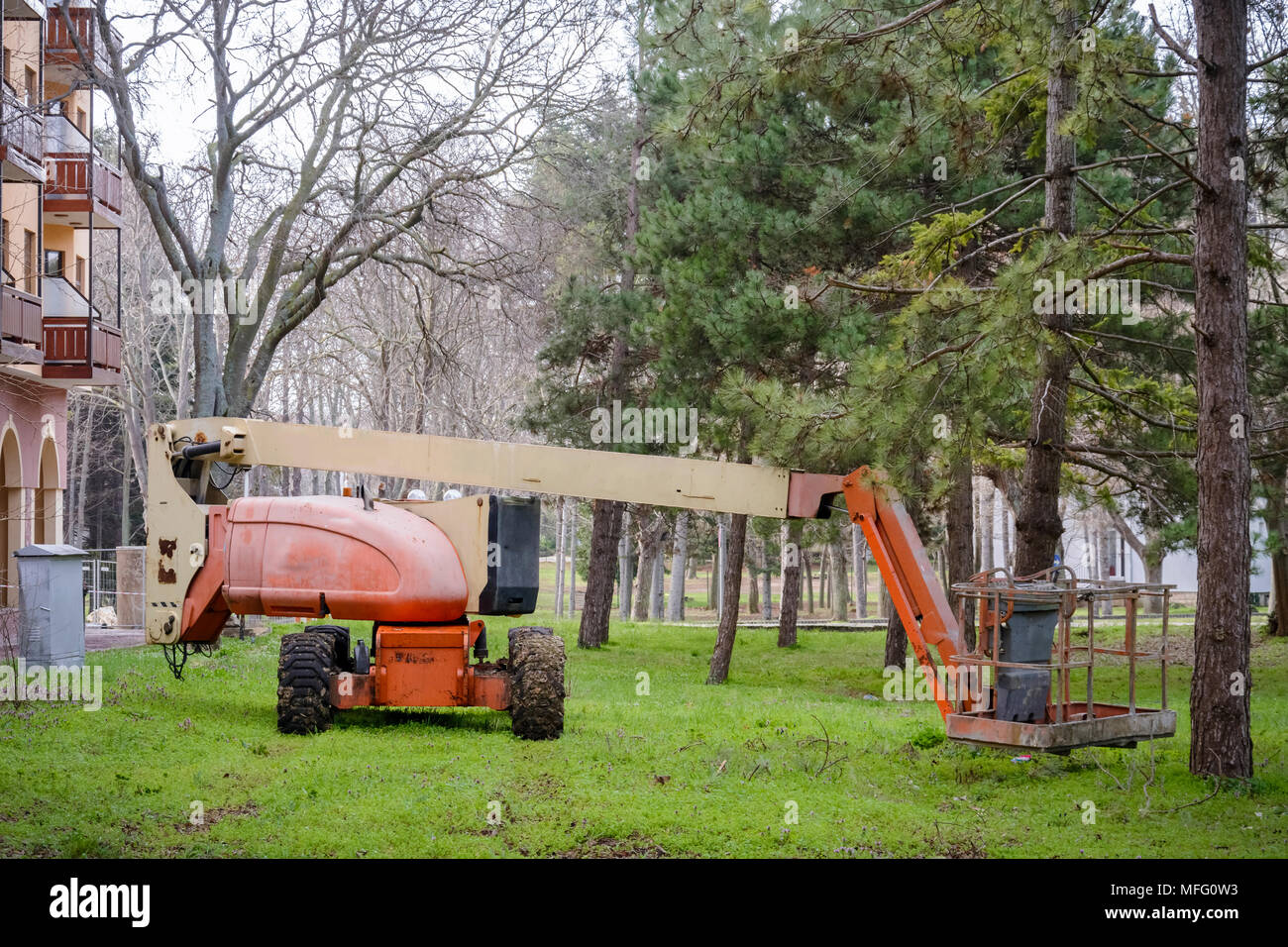 Articulated Boom Lift in the grass in a park - Stock Image