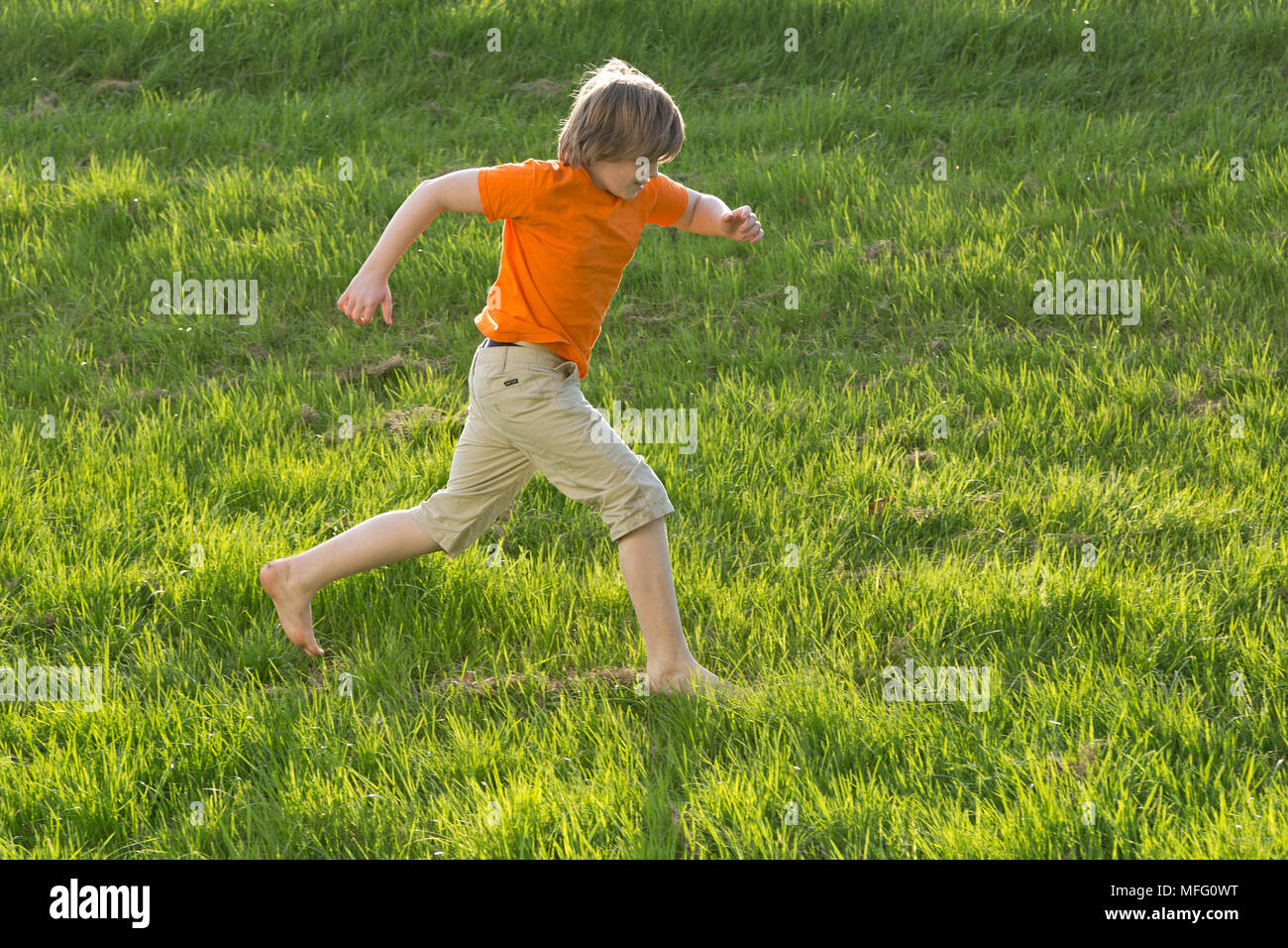 boy running across a meadow in his bare feet - Stock Image