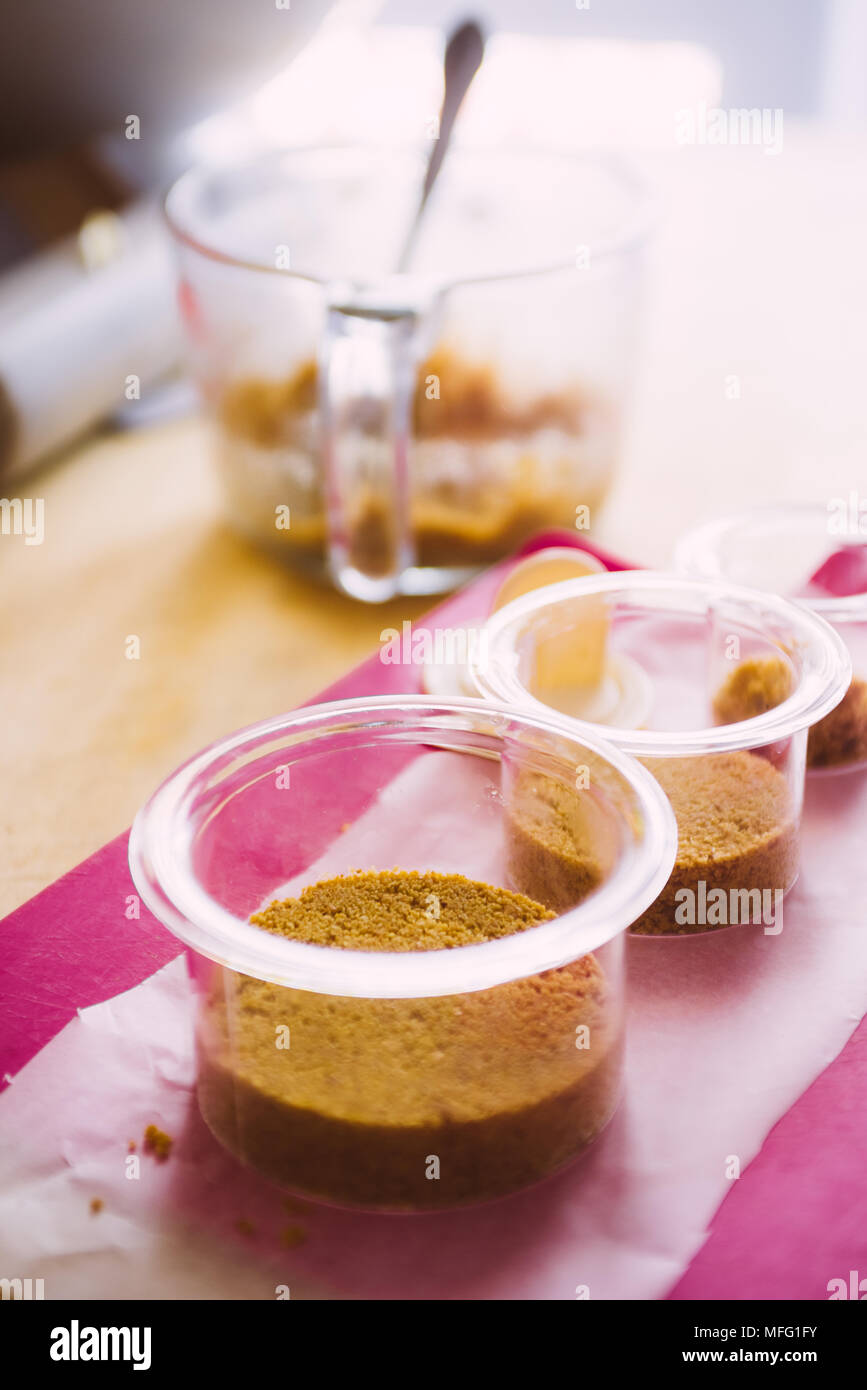 Plastic circular   cntainer are filled with granulated biscuits and butter then pressed to ccreate the base of chesecake dessert, cooking concept, ove - Stock Image