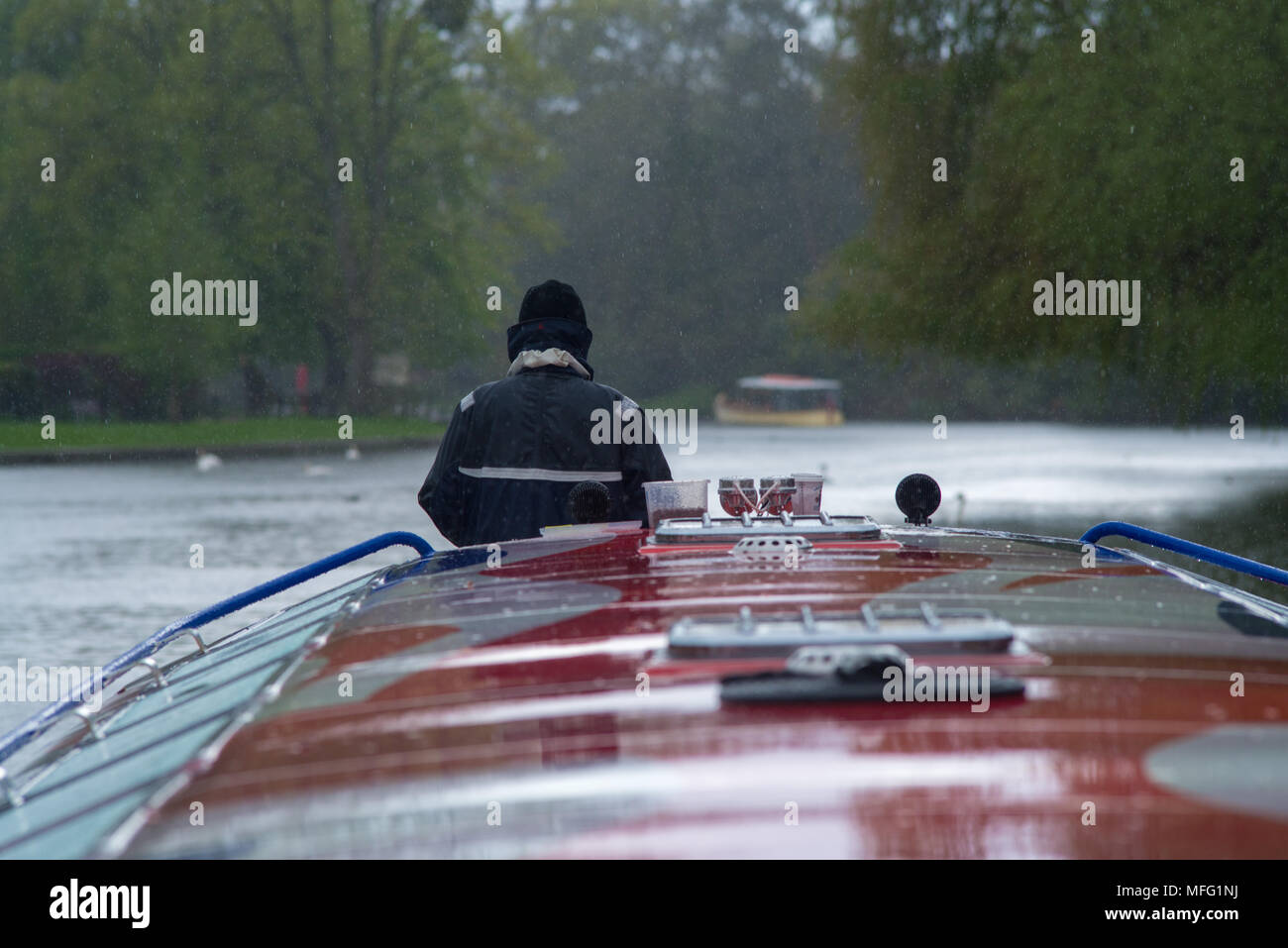 man on bow of boat in the a rain storm - Stock Image