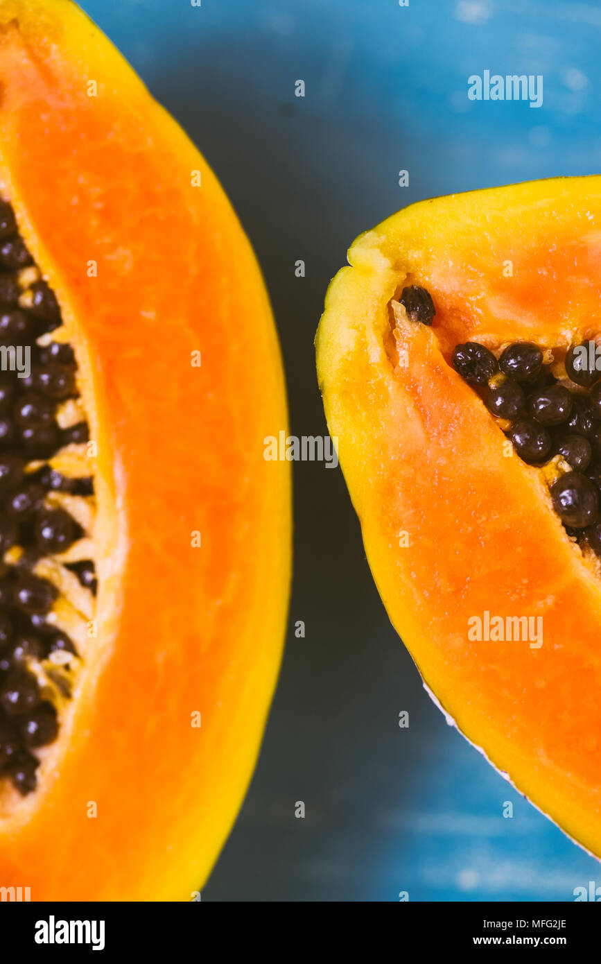 Close up of tropical fruit papaya cut i half on a wooden background - Stock Image
