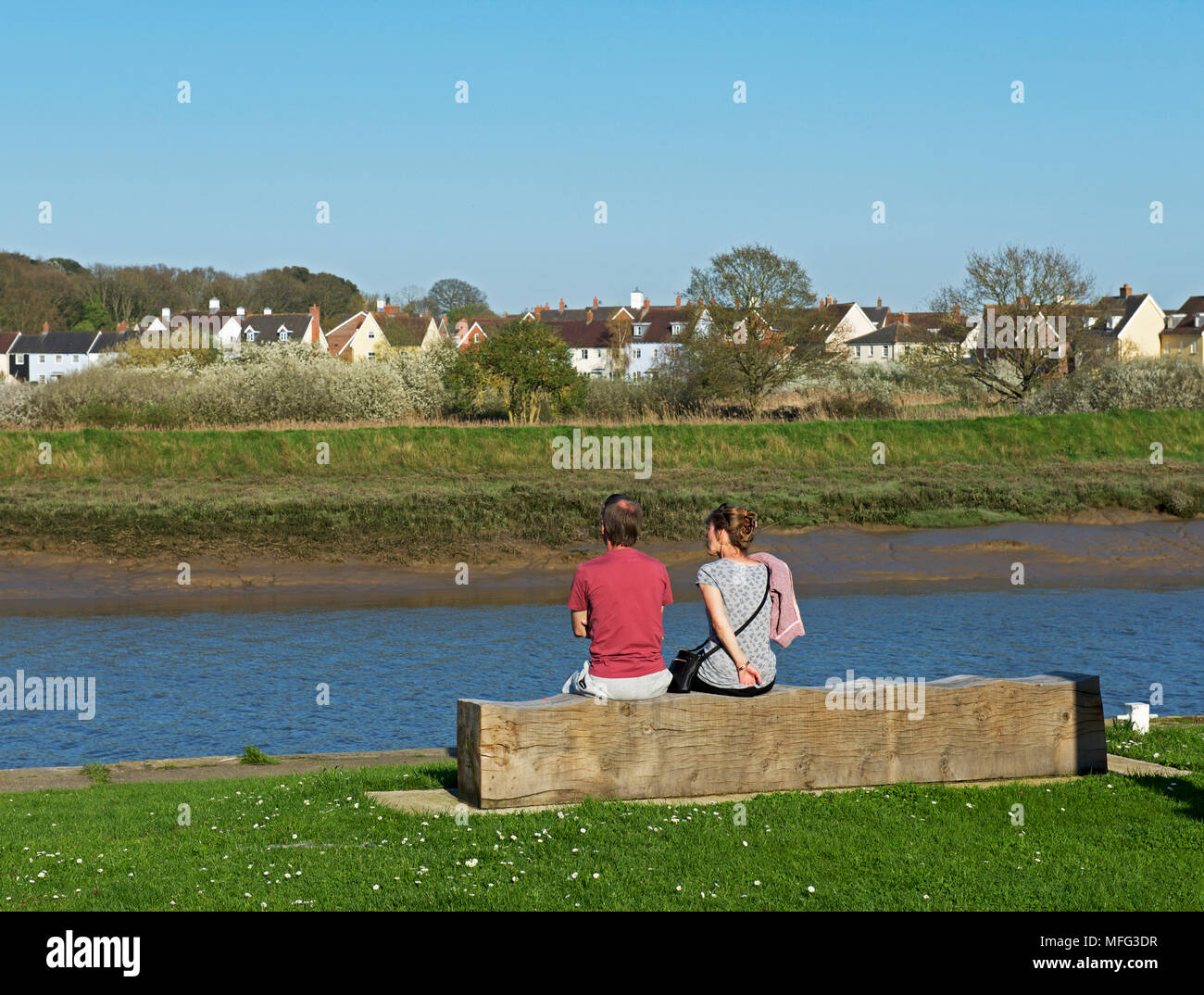 Couple sitting on bench overlooking the River Colne (and Wivenhoe), Essex, England UK - Stock Image