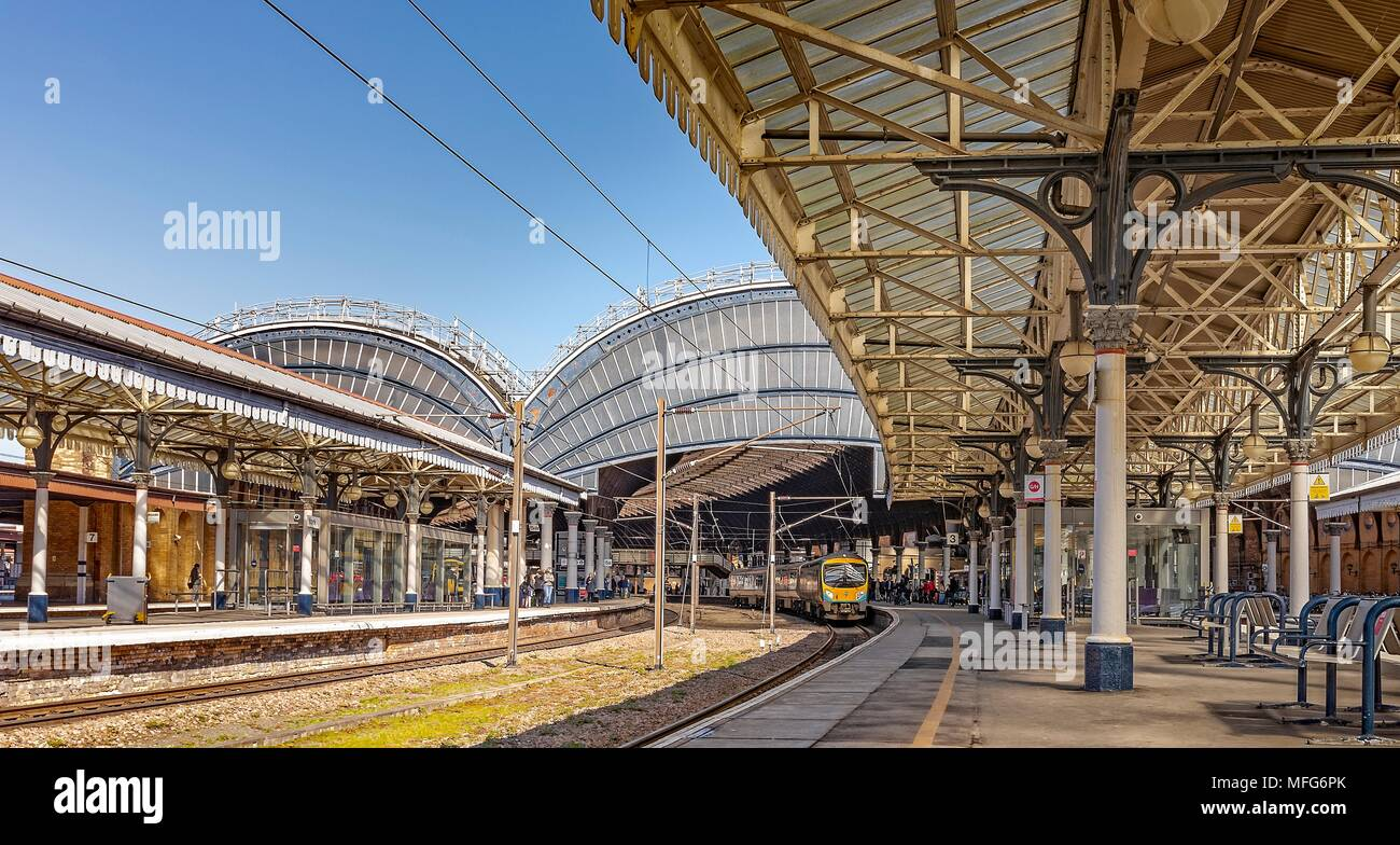 Classic view of a railway station.  A train is at the platform waiting to depart.  Overhead are ornate 19th Centrury canopies. - Stock Image