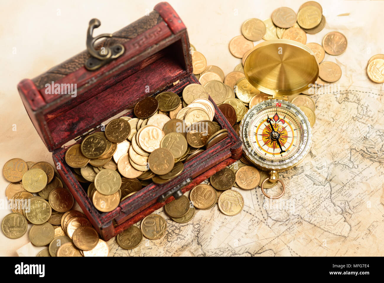 Open treasure chest filled with gold colored coins and compass over medieval world map - Stock Image