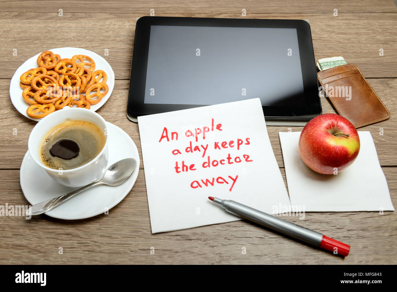 napkin handwriting message proverb on wooden table with coffee, some food and tablet PC An apple a day keeps the doctor away - Stock Image