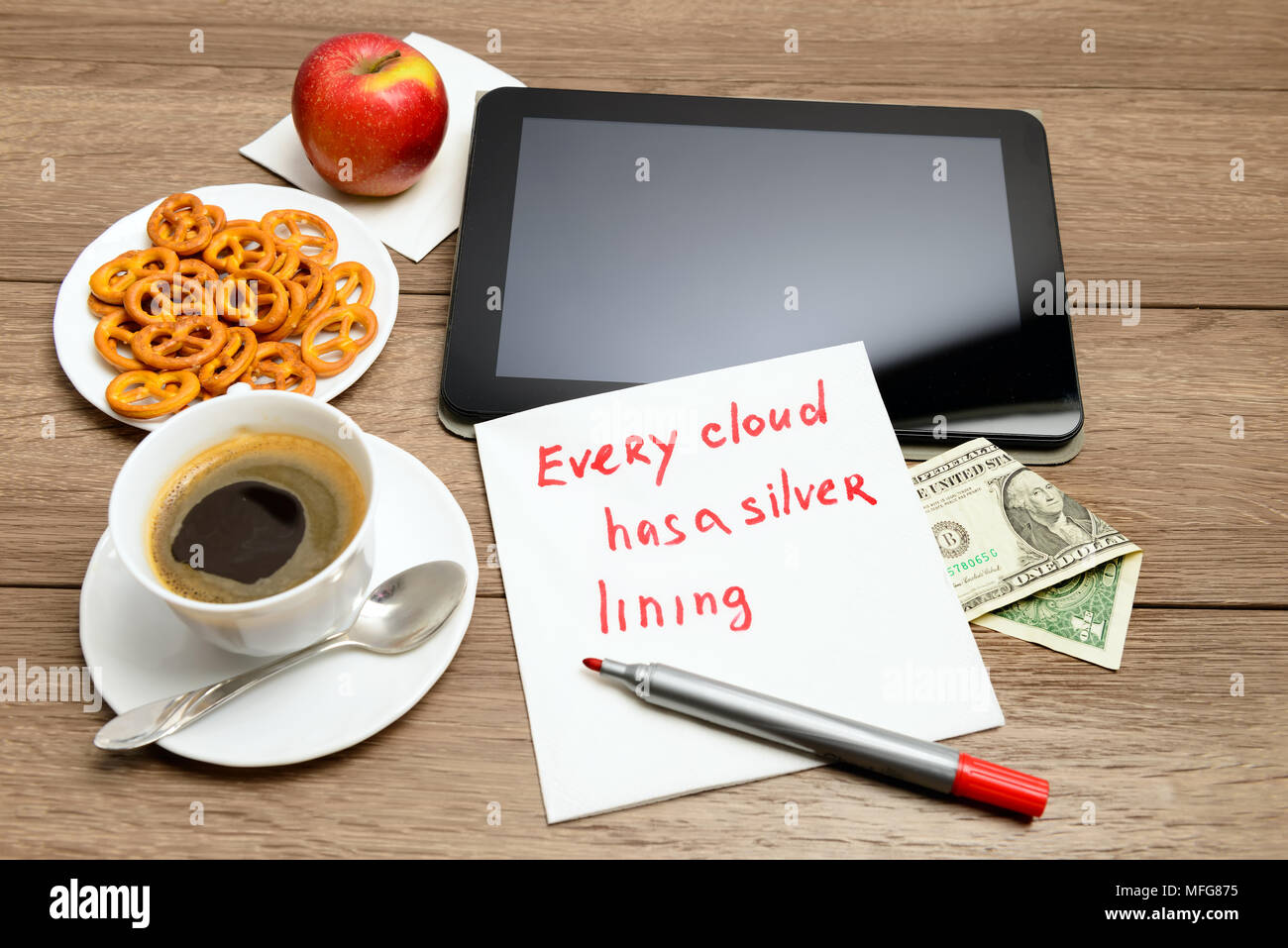 Wooden table with coffee, some food and napkin message proverb Every cloud has a silver lining - Stock Image