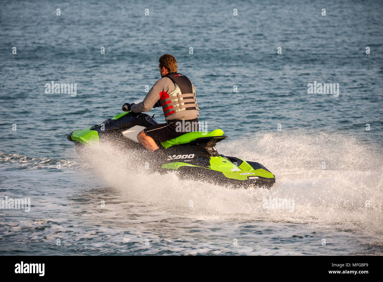 Middle aged man wearing a life vest rides a personal water craft Jet Ski along a calm sea. - Stock Image