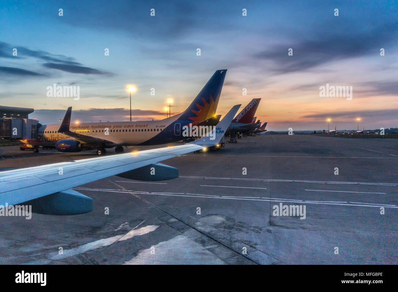 Window view from an aeroplane window looking across manchester airport runway at sunrise. - Stock Image