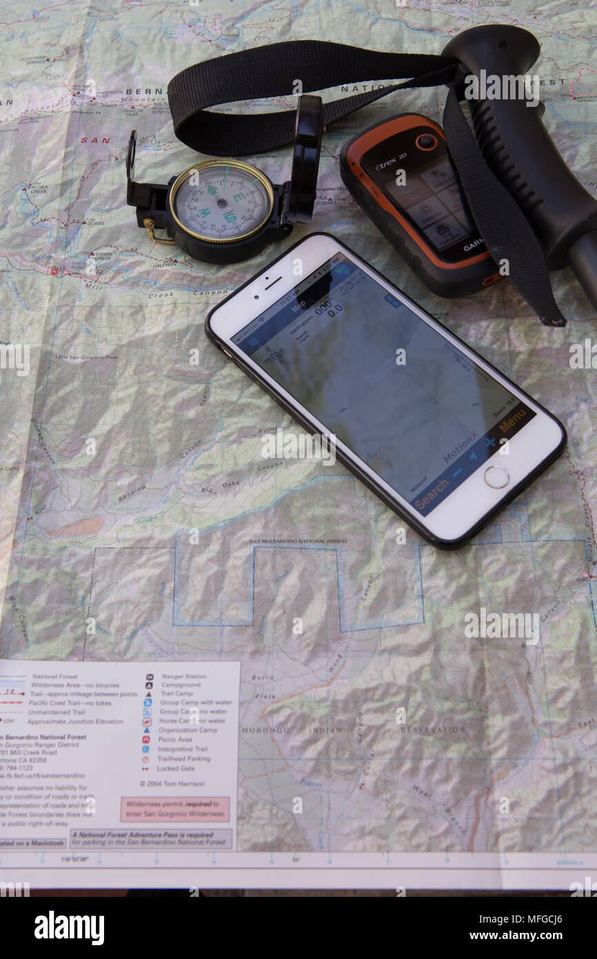 A number of different handheld navigational devices . Map,compass,iPhone with a gps app and a Garmin  GPS - Stock Image