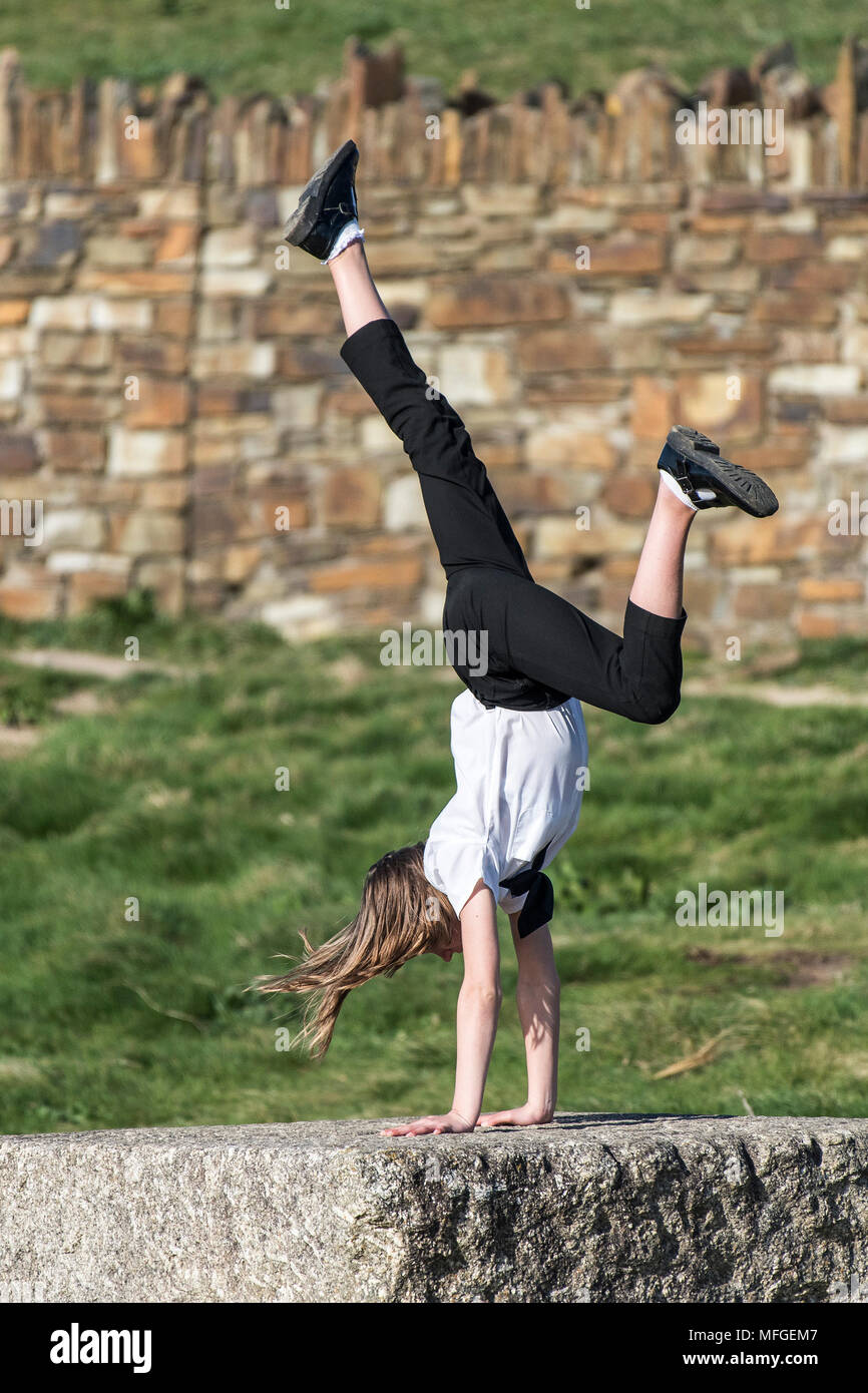 A young teenager performing a handstand on a block of granite. - Stock Image