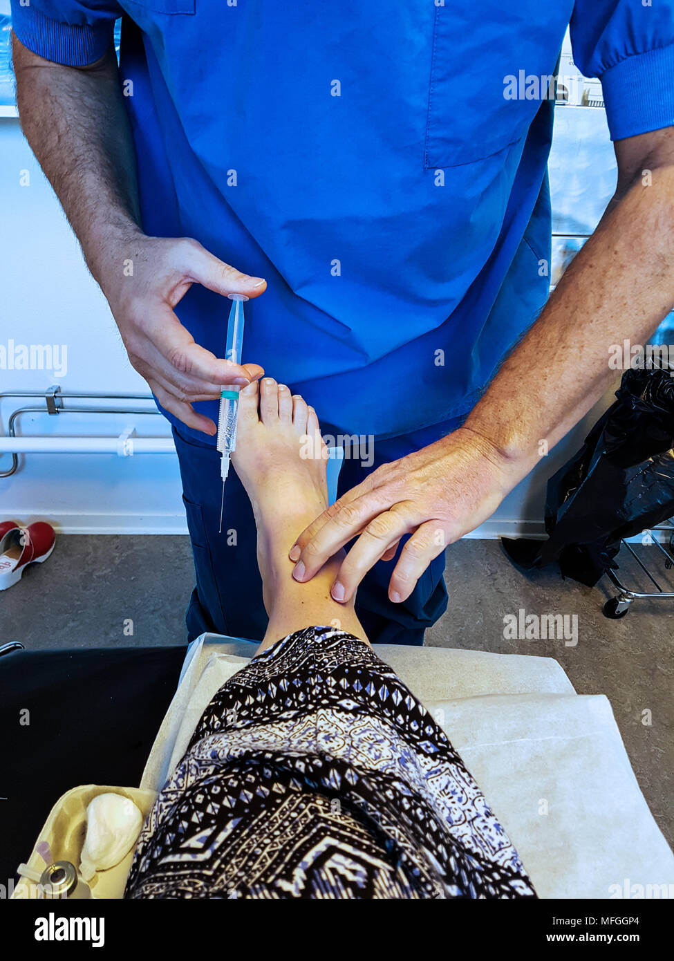 A doctor is injecting local anesthetic in the patients foot in preparation for surgery of a tailor's bunion. - Stock Image