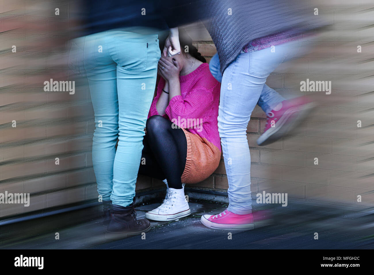 Teenage girls bullying and kicking a girl sitting down covering her face, crying. Blurred. - Stock Image