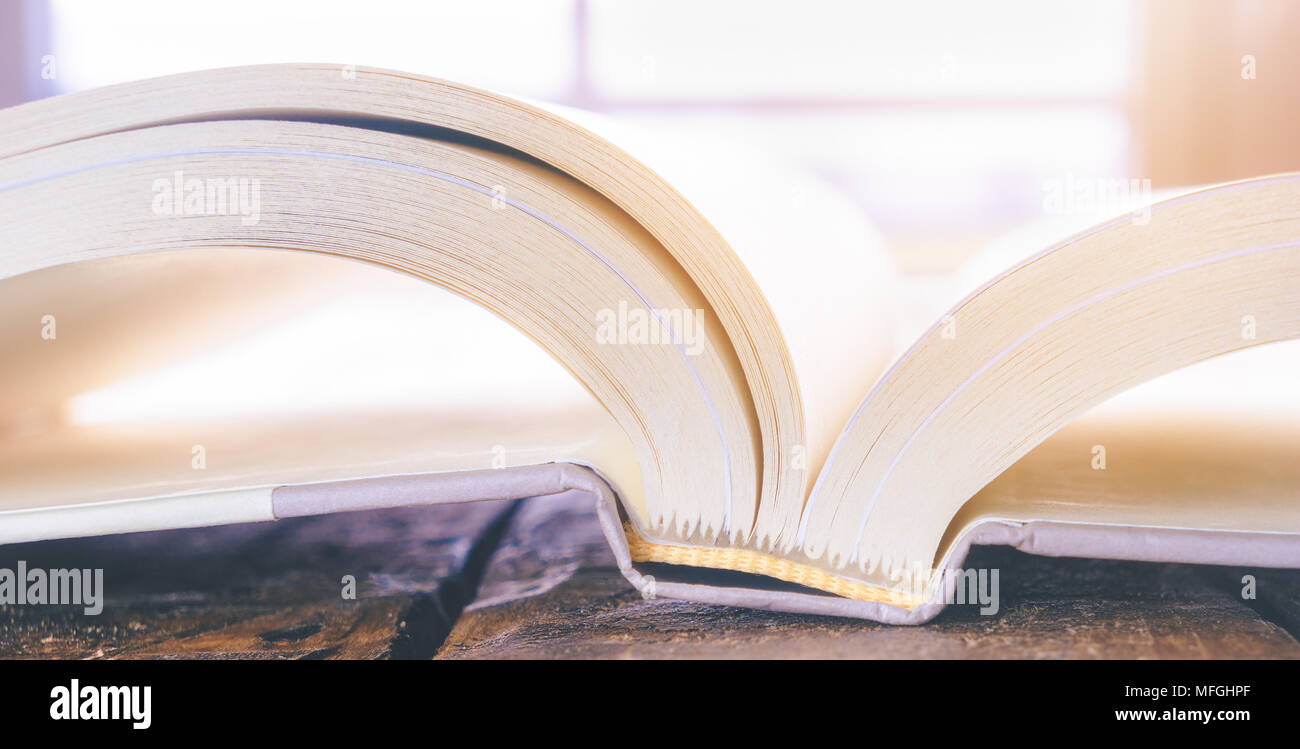 High key closeup of an open book with white pages, reading and literacy concept. - Stock Image