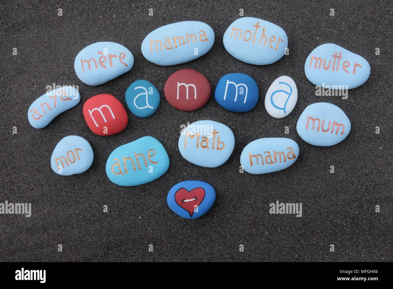 Mother text in many languages with carved and colored stones over black volcanic sand - Stock Image