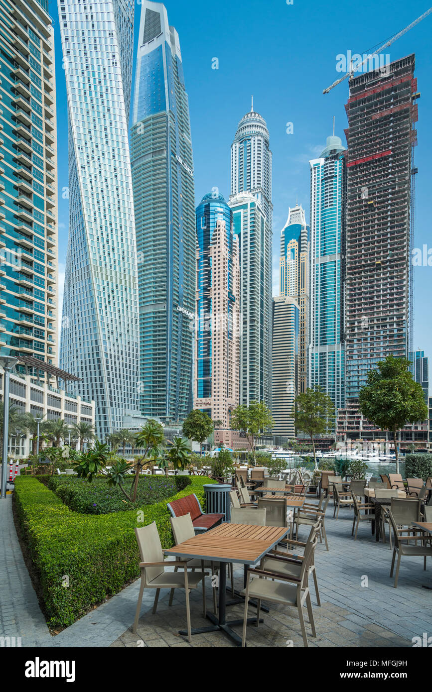 An outdoor restaurant and tall buildings of the Dubai marina, UAE, Middle East. - Stock Image