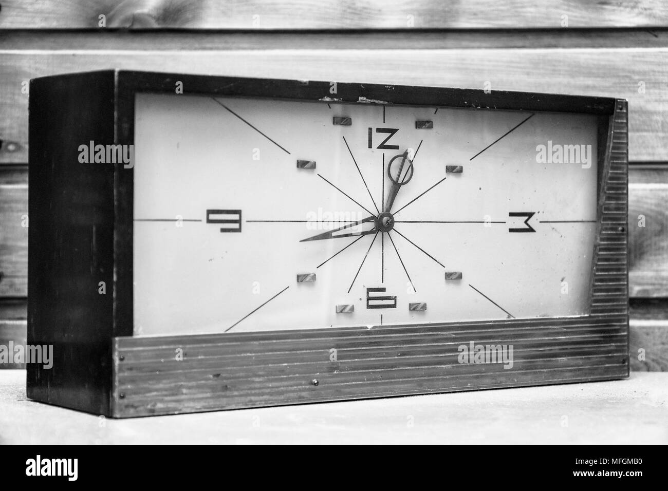 Old Rectangular clock on the background of wooden wall - Stock Image