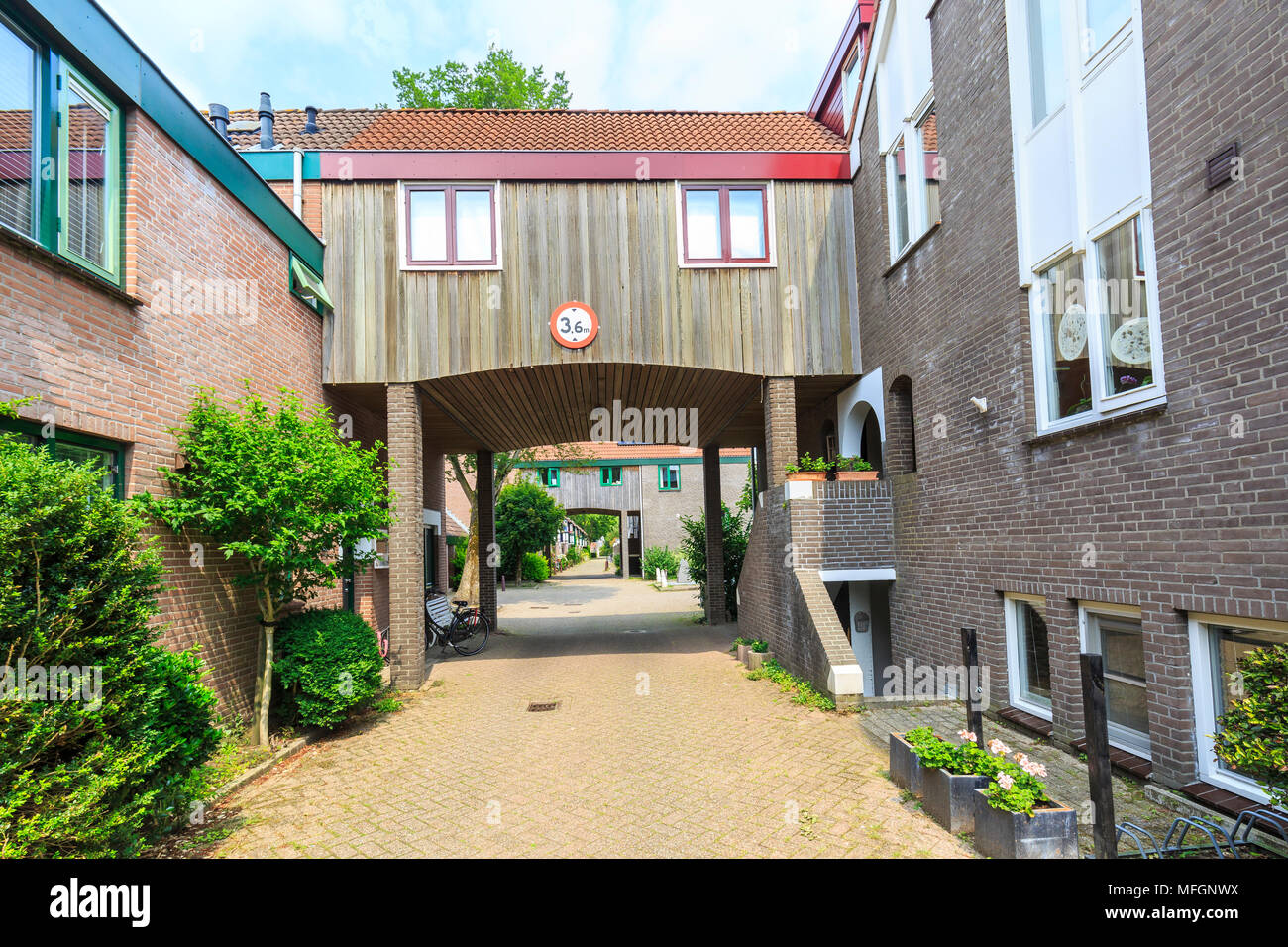 Modern style build residential wooden passageway structure building in a street with homes and houses with a height limt sign
