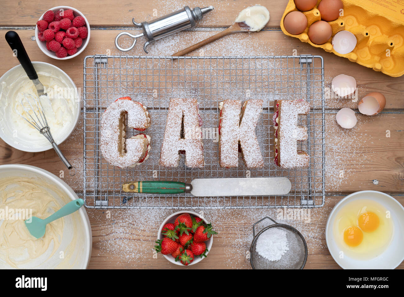 Victoria raspberry and strawberry cream sponge cakes spelling the word CAKE with ingredients from above. Pattern - Stock Image