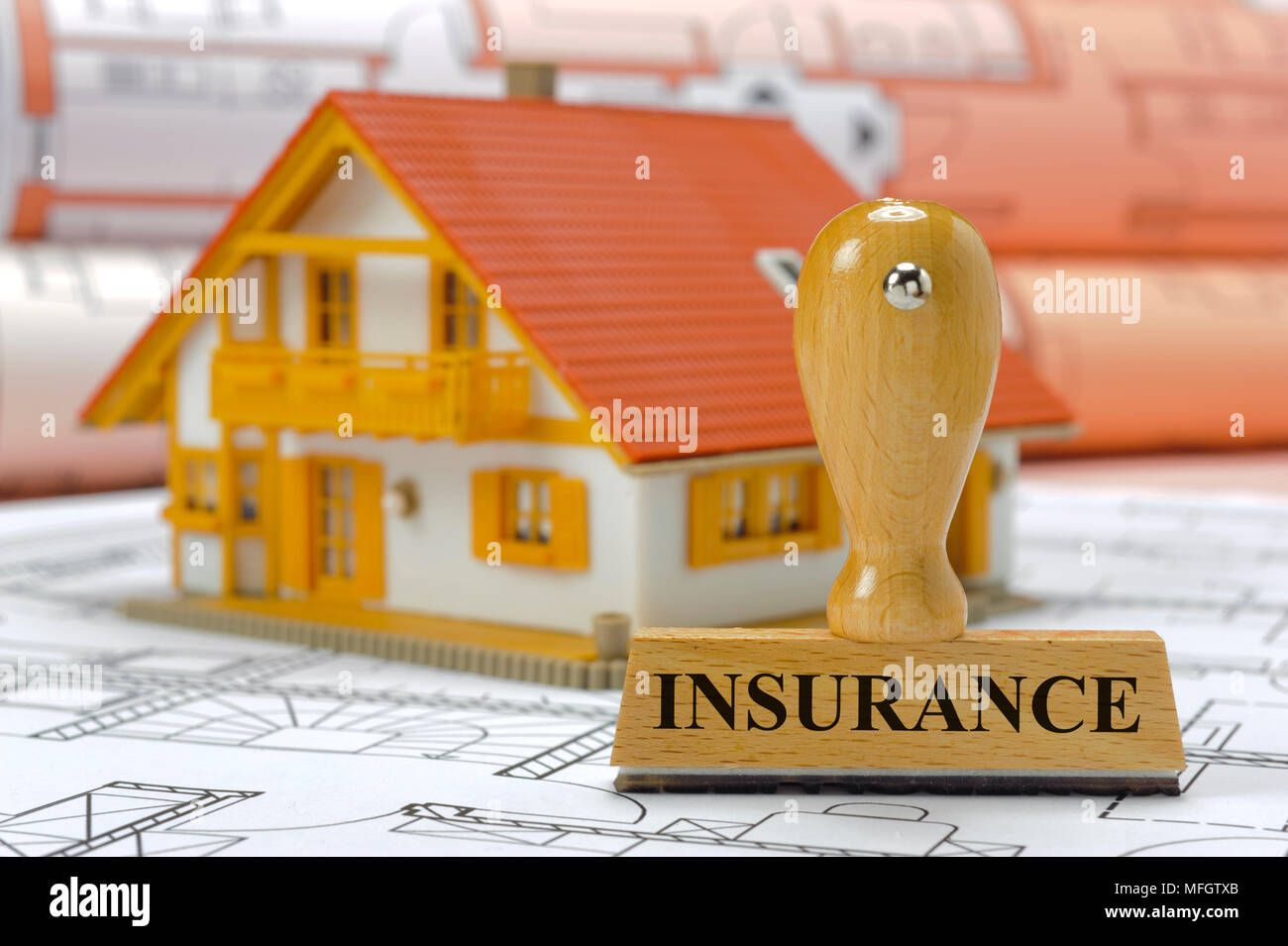 insurance marked on rubber stamp with model house and construction plan - Stock Image