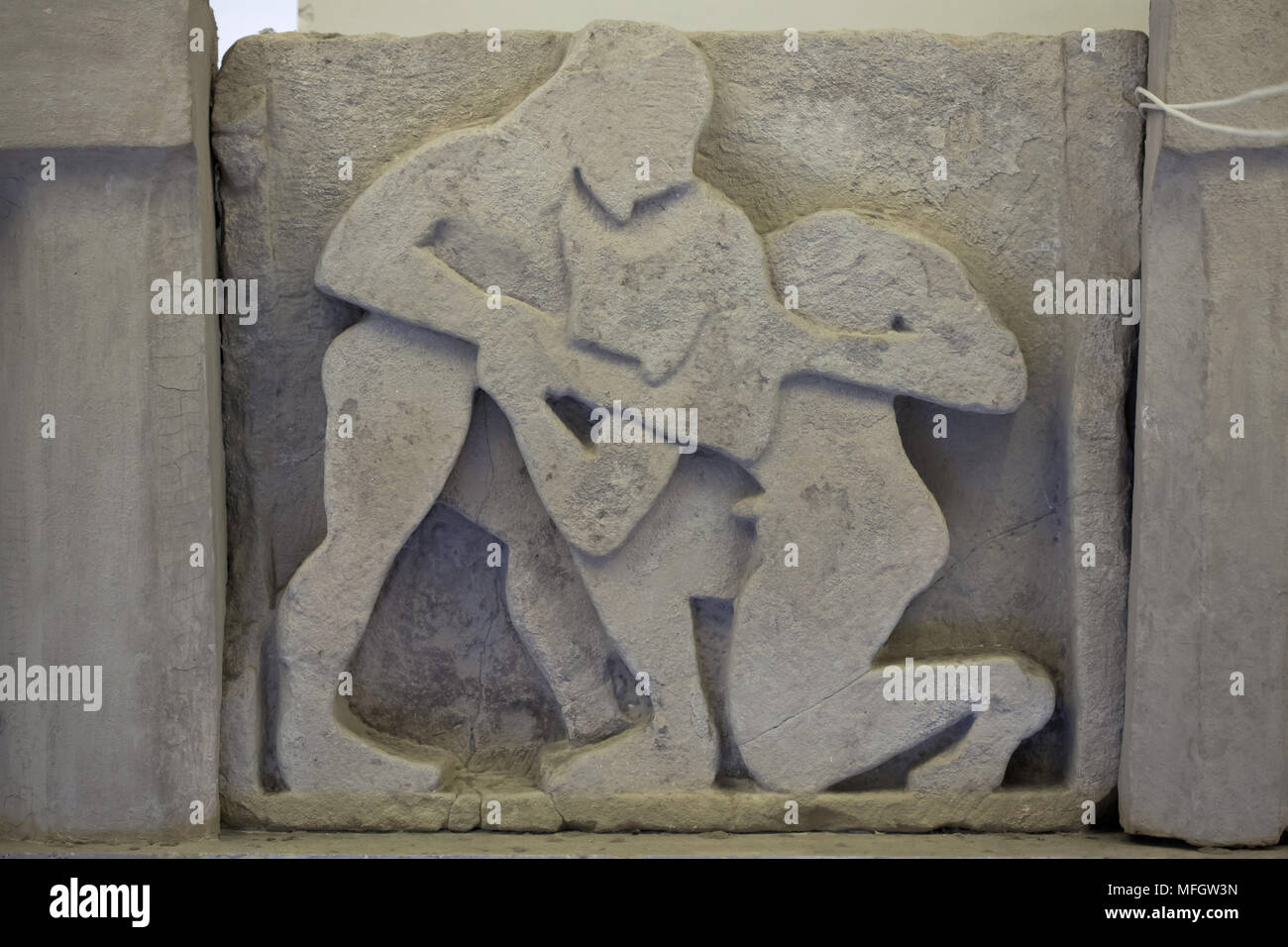 Heracles fighting Antaeus. Archaic sandstone metope from the Heraion (First Temple of Hera) at Foce del Sele dated from the middle of the 6th century BC on display in the Paestum Archaeological Museum (Museo archeologico di Paestum) in Paestum, Campania, Italy. - Stock Image