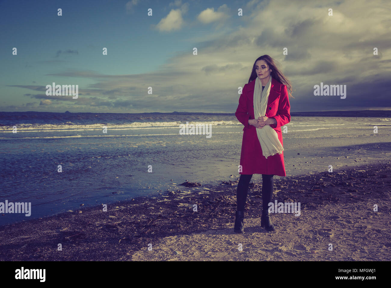 Woman in red jacket on a beach. - Stock Image