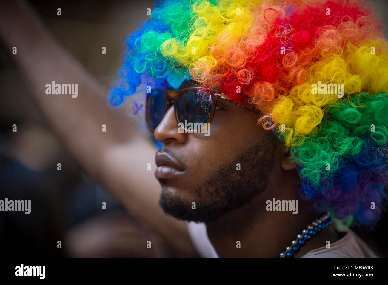 NEW YORK CITY - JUNE 25, 2017: Supporter in a rainbow afro wig on the sidelines of the annual Pride Parade as it passes through Greenwich Village. - Stock Image