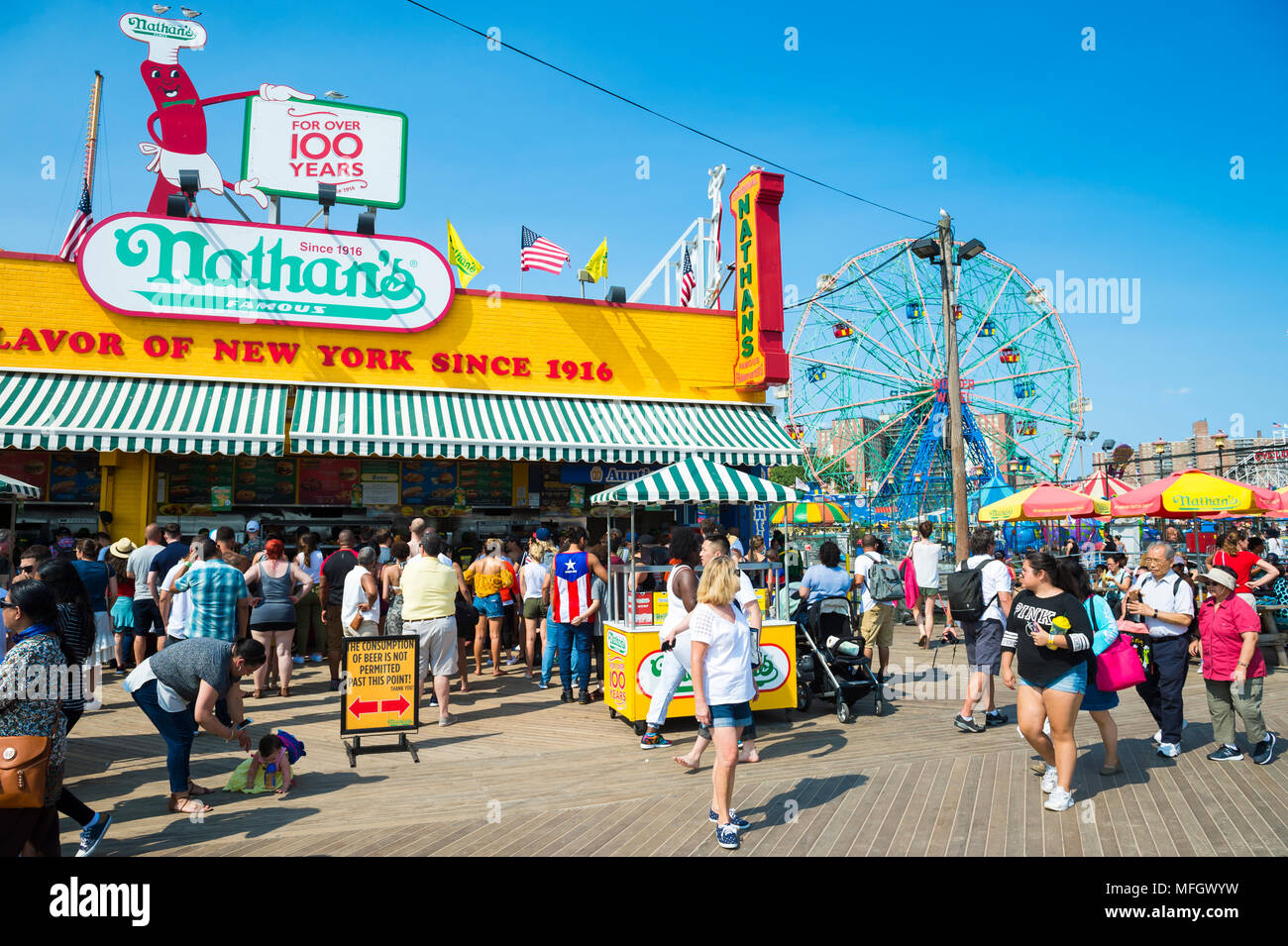 NEW YORK CITY - AUGUST 20, 2017: Visitors walk the iconic wooden Coney Island boardwalk outside the famous Nathan's hot dog stand on a hot summer day - Stock Image