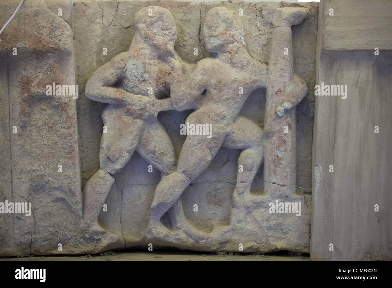 Orestes kills Aegisthus. Archaic sandstone metope from the Heraion (First Temple of Hera) at Foce del Sele dated from the middle of the 6th century BC on display in the Paestum Archaeological Museum (Museo archeologico di Paestum) in Paestum, Campania, Italy. - Stock Image