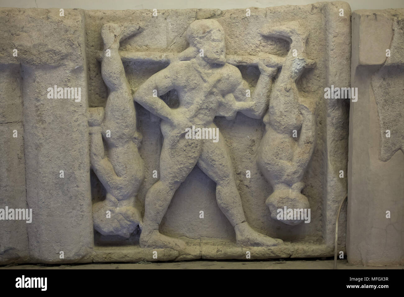 Heracles punishing the Cercopes. Archaic sandstone metope from the Heraion (First Temple of Hera) at Foce del Sele dated from the middle of the 6th century BC on display in the Paestum Archaeological Museum (Museo archeologico di Paestum) in Paestum, Campania, Italy. - Stock Image