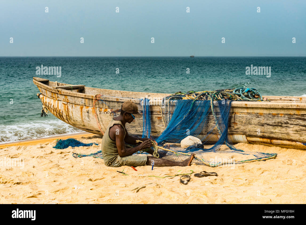 Man fixing their nets in their fishing boats on a beach in Robertsport, Liberia, West Africa, Africa - Stock Image