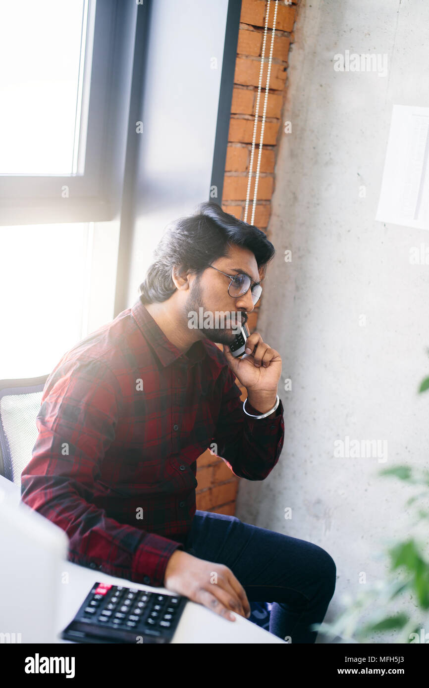 closeup side view shot of brutal Hindoo accountant inspector with smartphone in the loft office - Stock Image