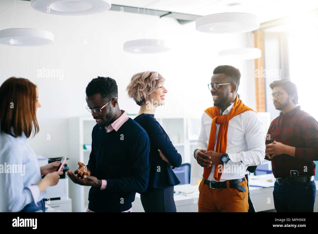 close up portrait of young multi ethnic people talking in pairs. new methods of comunication in the office - Stock Image