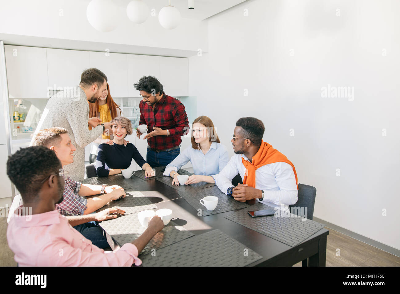 African man in checked shirt and Caucasian man in white sweater are standing next to their female colleague and making their case. two men proving the - Stock Image