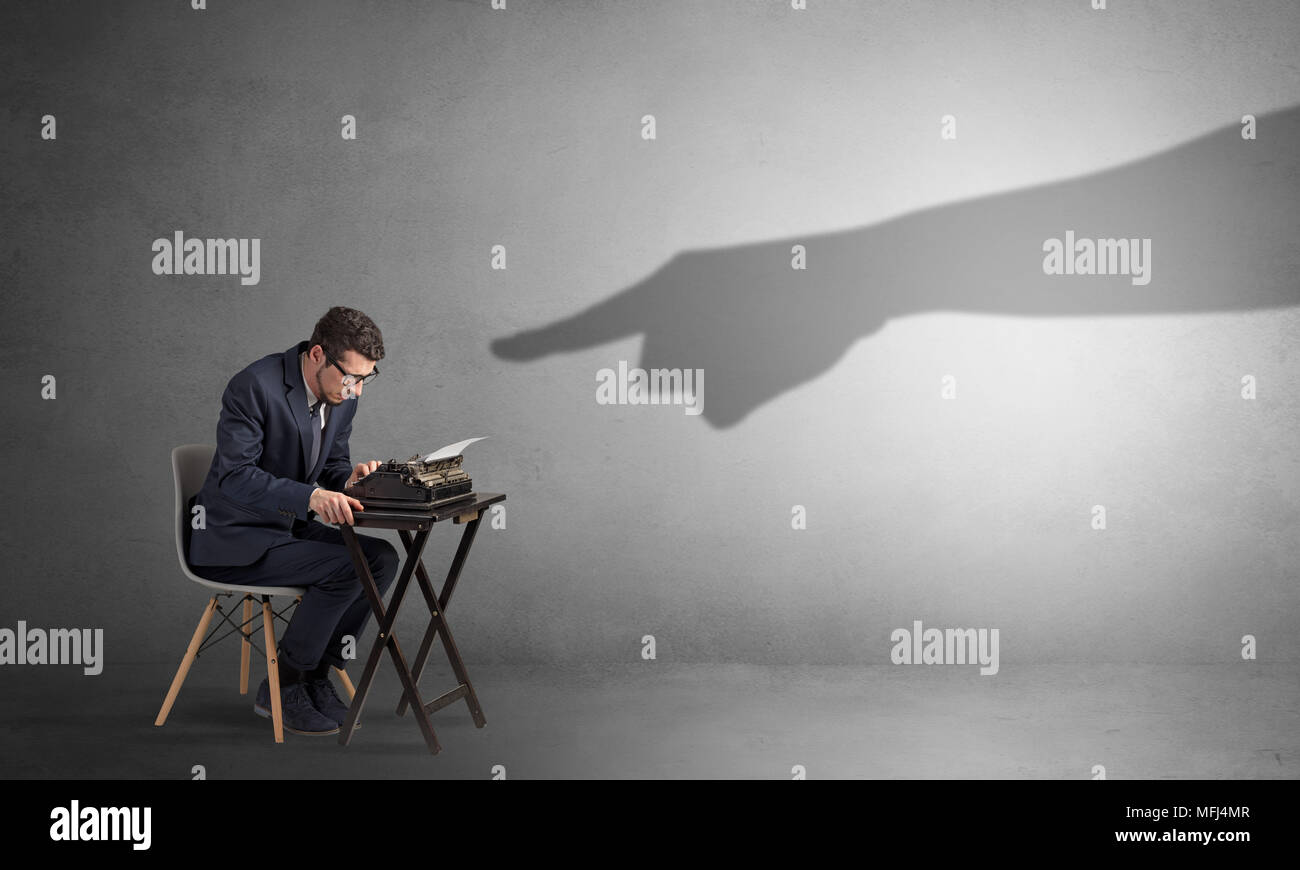 Shadow hand pointing at a small afraid worker  - Stock Image