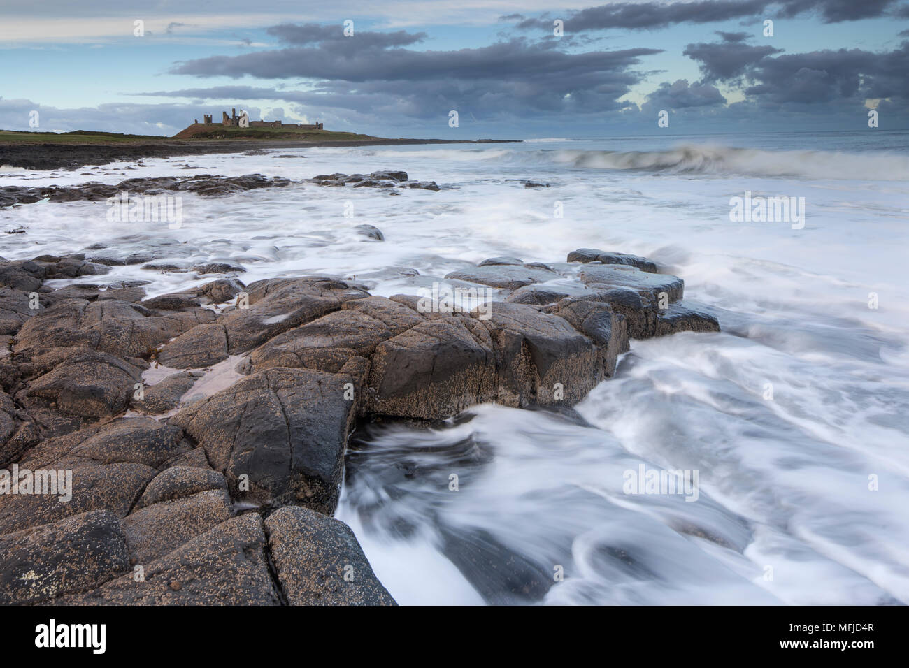Dunstanburgh castle from the rocky shore close to Craster, Northumberland, England, United Kingdom, Europe - Stock Image