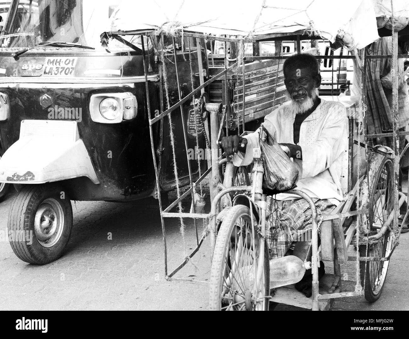 Old man amputee competing with the traffic on a hand powered rickshaw on a Mumbai street, India - Stock Image
