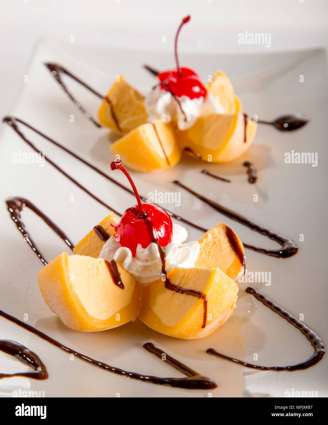 A plate with two servings of Mango Mochi ice cream topped with whip cream and cherries. - Stock Image