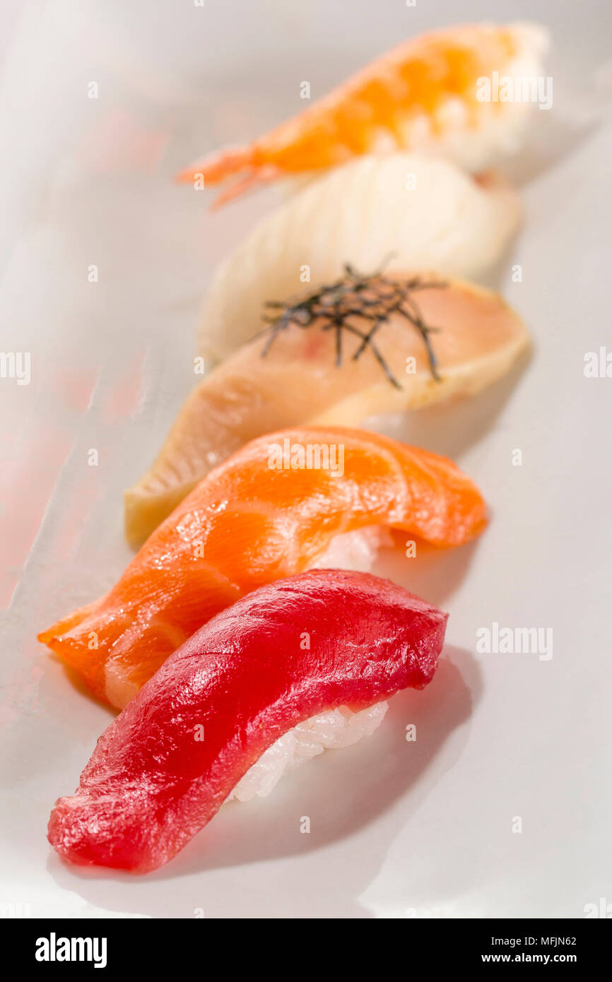 A variety of sushi on a platter in a restaurant. - Stock Image