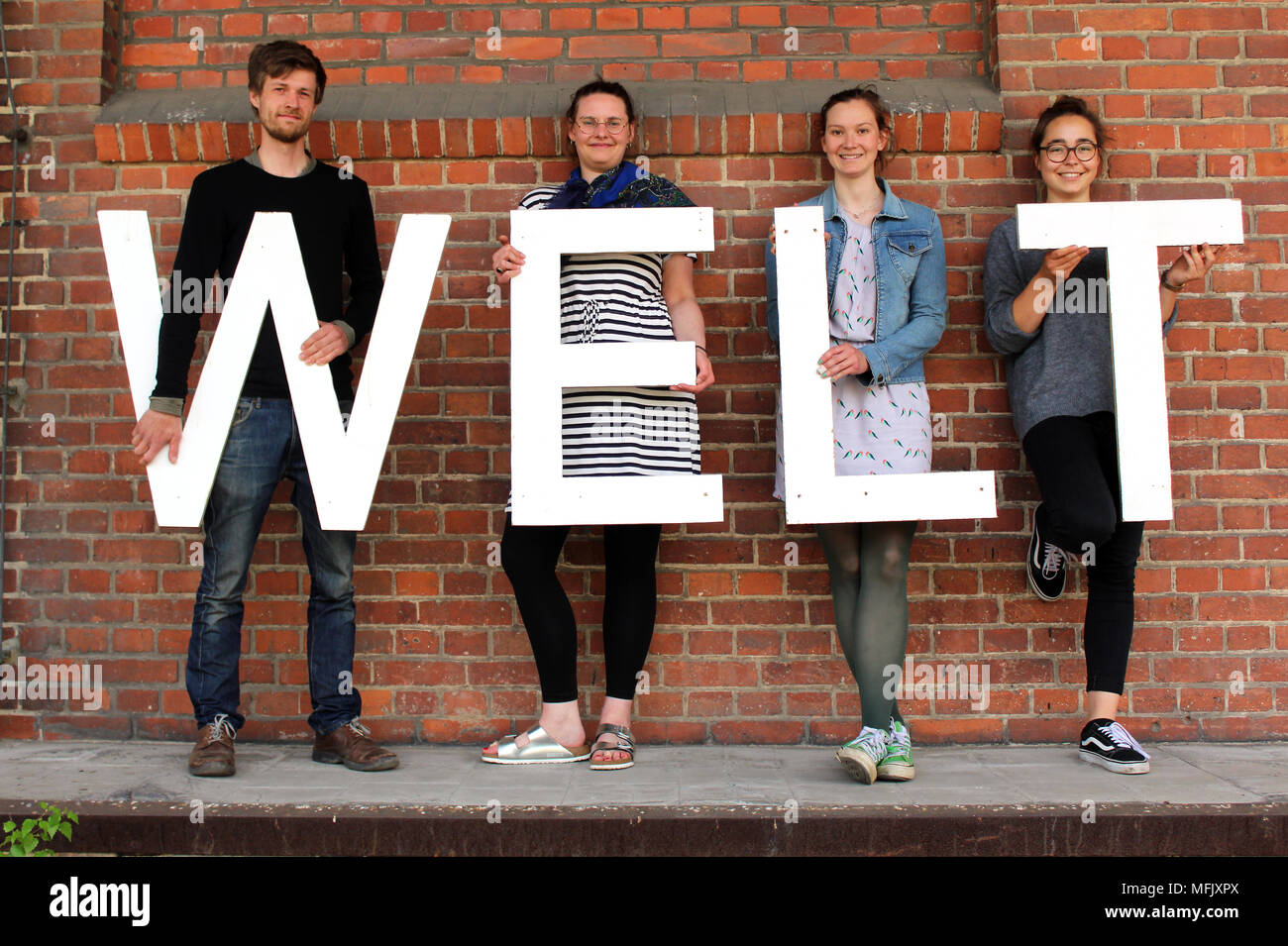23 April 2018, Germany, Goerlitz: Students Lorenz Kallenbach (L-R), Michaela Jarosch, Lisa Schaefer and Josephine Junker holding the letters that make up the word 'Welt' (Lit. world). The students and young artist are organising the exhibition 'Weltstadt'(lit. world city Goerlitz) in an empty freight depot. Photo: Miriam Schönbach/dpa-Zentralbild/dpa - Stock Image