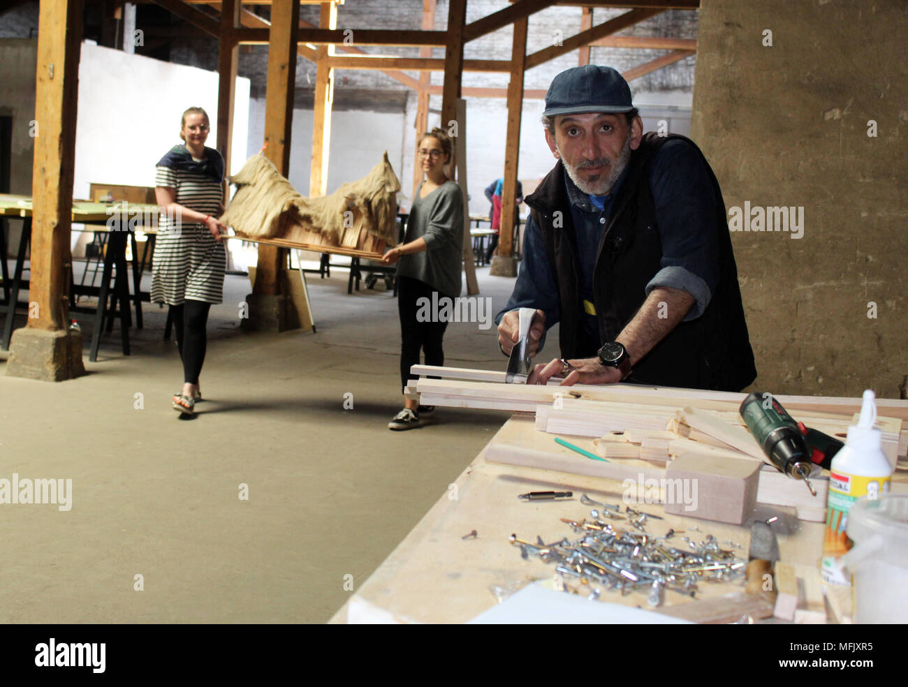 23 April 2018, Germany, Goerlitz: Hussein Daowdi from Syria vuilding a model house for the Goerlitz quarter at the exhibition 'Weltstadt' (lit. world city) and in the background students Michaela Jarosch (L) and Josephine Junker. Photo: Miriam Schönbach/dpa-Zentralbild/dpa - Stock Image
