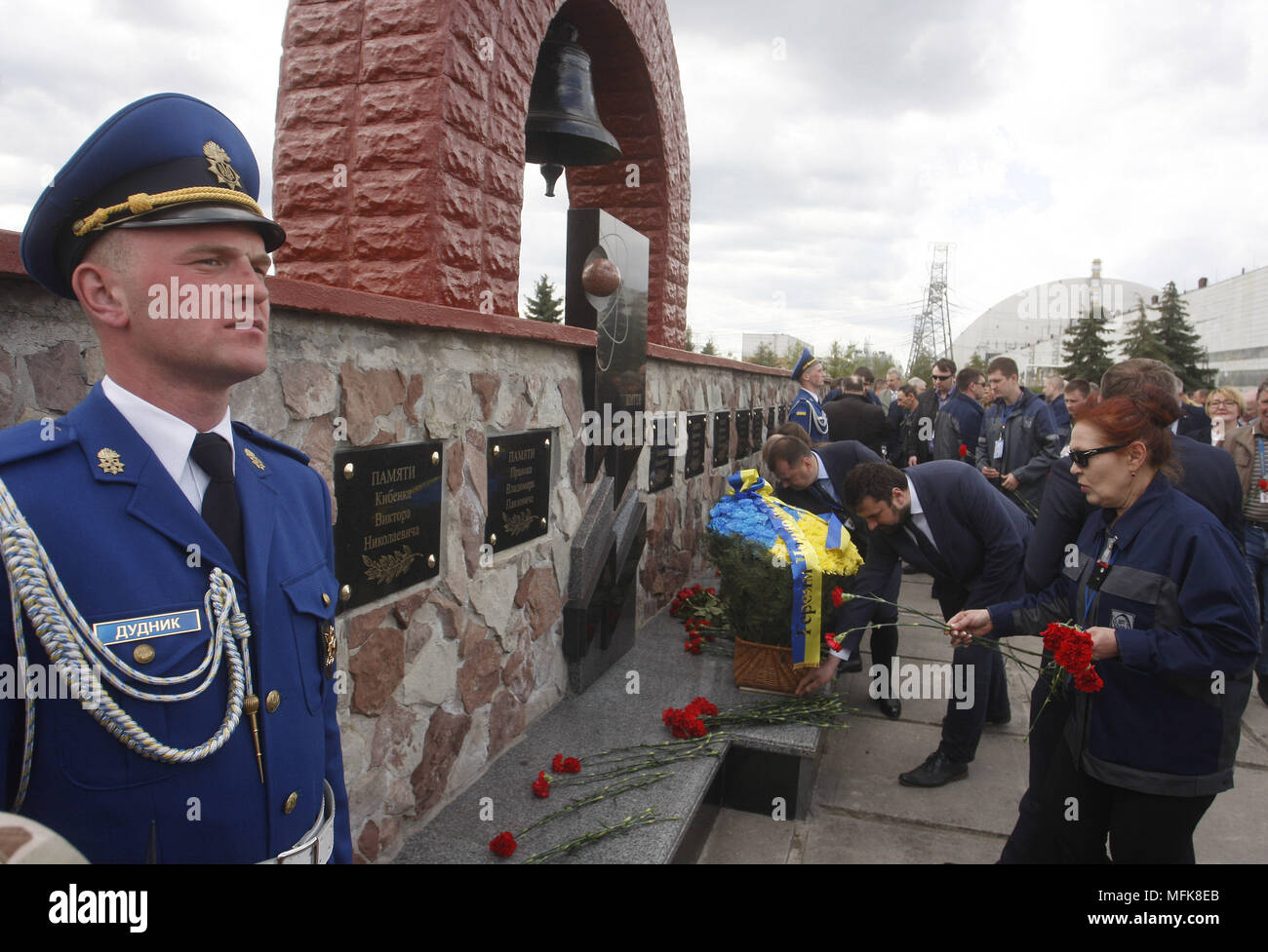 Kiev, Ukraine. 26th Apr, 2018. Chernobyl power plant workers lay flowers to the monument honoring people who were killed in the Chernobyl nuclear power plant disaster, during a ceremony in Chernobyl, Kiev region, Ukraine, on 26 April 2018. Ukrainians mark the 32th anniversary of Chernobyl's tragedy. The explosion of Unit 4 of the Chernobyl nuclear power plant on 26 April 1986 is still regarded the biggest accident in the history of nuclear power generation. Credit: Serg Glovny/ZUMA Wire/Alamy Live News - Stock Image