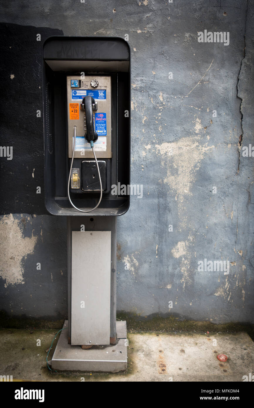 A pay telephone in front of a blue wall with peeling paint - Stock Image