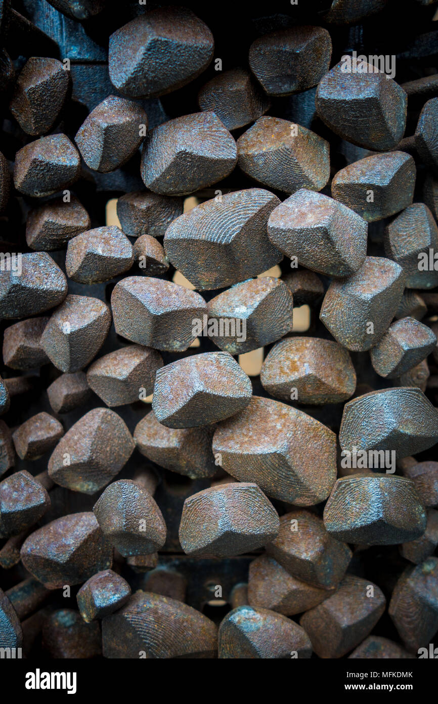 Large industrial metal nail heads form an unusual and interesting pattern on a wall - Stock Image