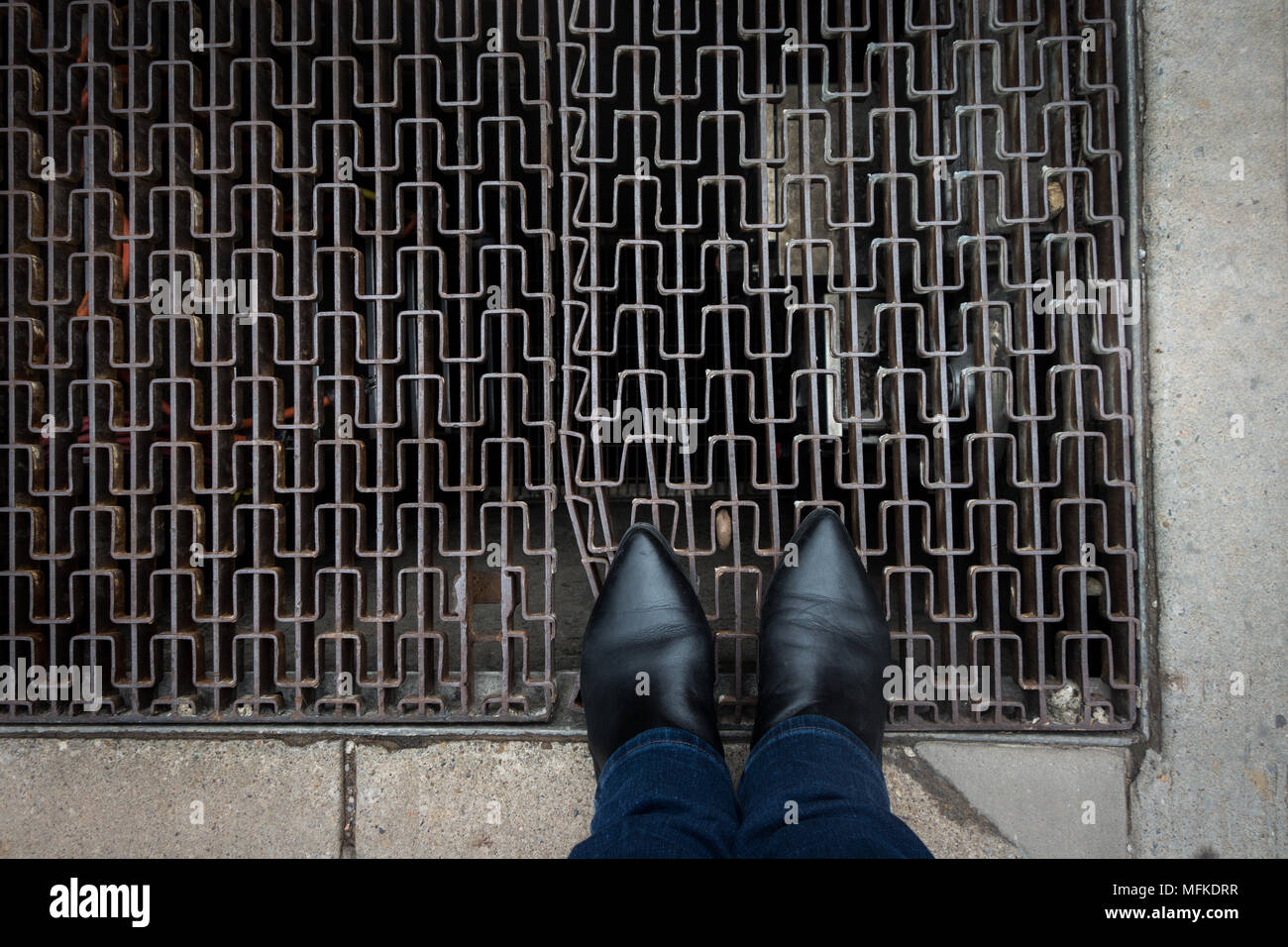 A person wearing pointy toed boots standing on a sidewalk grate - Stock Image
