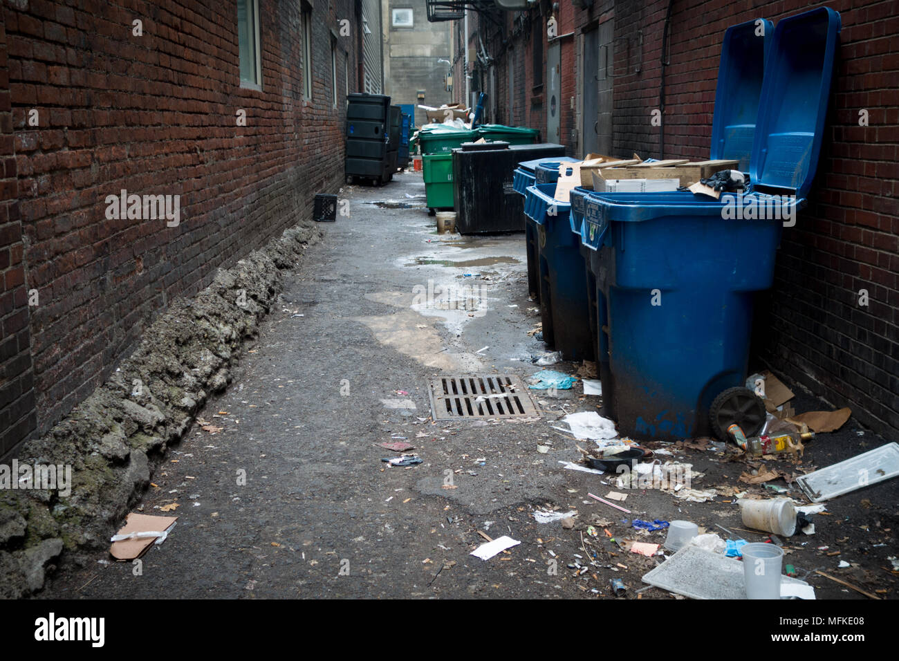 Large, overflowing garbage cans in a back alley in Pittsburgh, Pennsylvania, USA - Stock Image