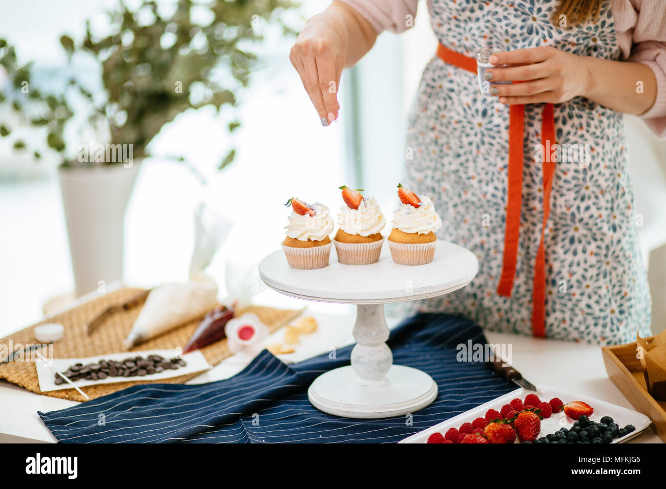Female baker in mottled dress decoratig creamy top cupcakes with coloured topping - Stock Image