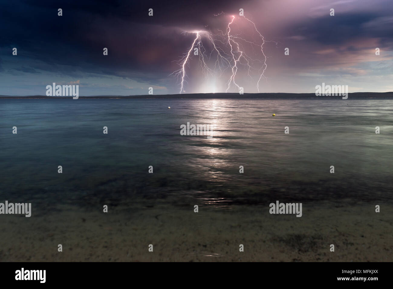 Spectacular lightning bolts over a calm ocean bay on an ominous, dark, contrasting stormy day. - Stock Image